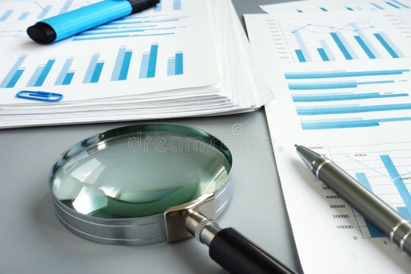 Förstoringsglas och affärsrapport för att revidera arkivfoton