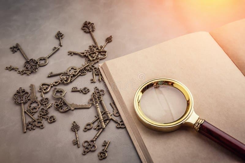 Förstoringsglas och en tangent på anteckningsboken för tom sida arkivbild
