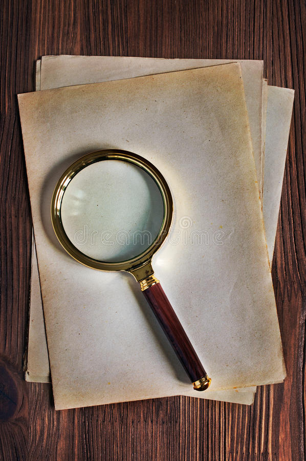 Förstoringsglas och gammalt gulnat ark av papper arkivbilder