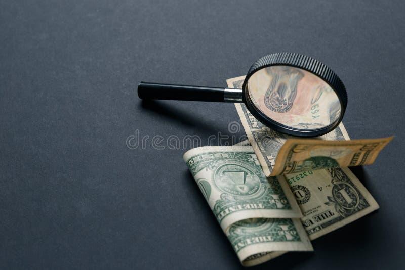 Förstoringsglas och pengar på svart bakgrund Pappers- valuta arkivfoton