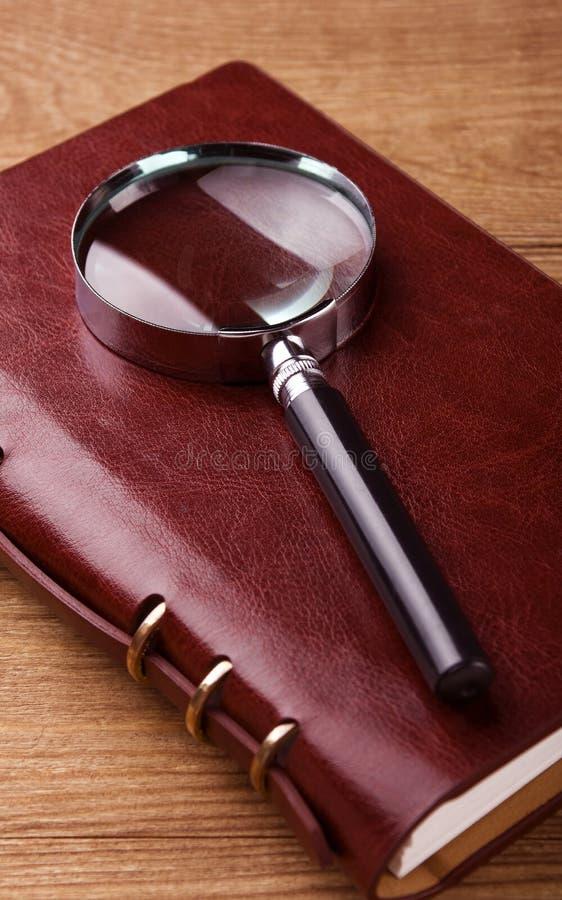 Förstoringsglas på anteckningsboken royaltyfri bild