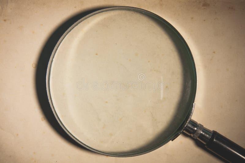 Förstoringsglas på den gamla pappers- bakgrunden royaltyfria foton