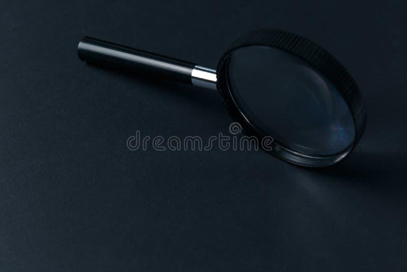 Förstoringsglas på svart textur arkivbild