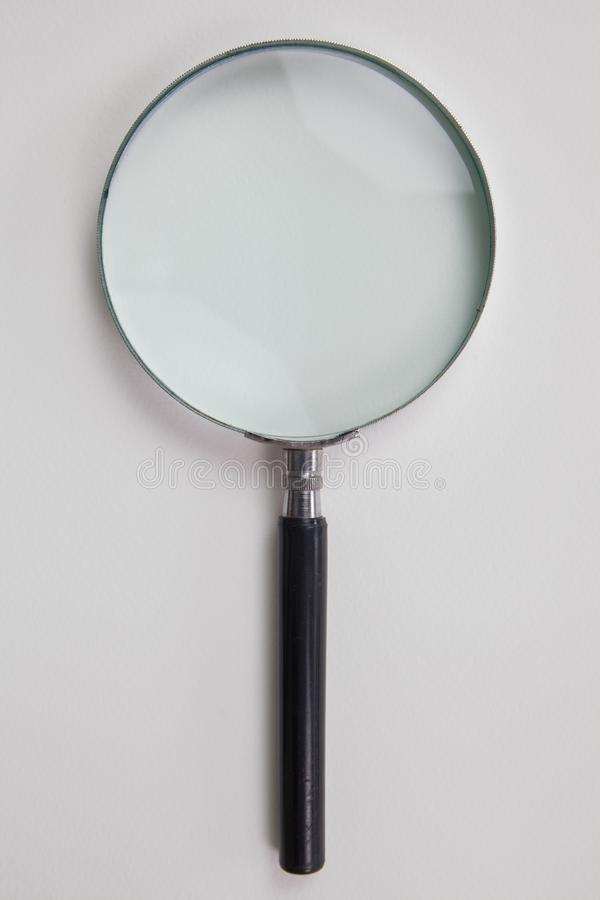 Förstoringsglas på vitbok royaltyfri foto
