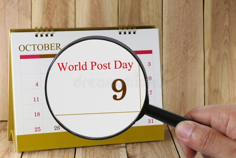 Förstoringsglaset i hand på kalender kan du se världsstolpedag arkivbild
