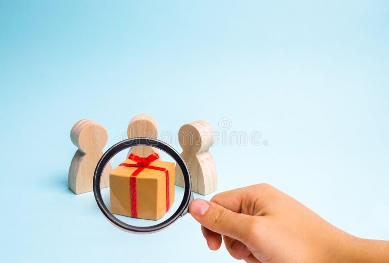 Förstoringsglaset ser folket som samlas runt om gåvan och, är klart att öppna den Familjferie, jul royaltyfri bild