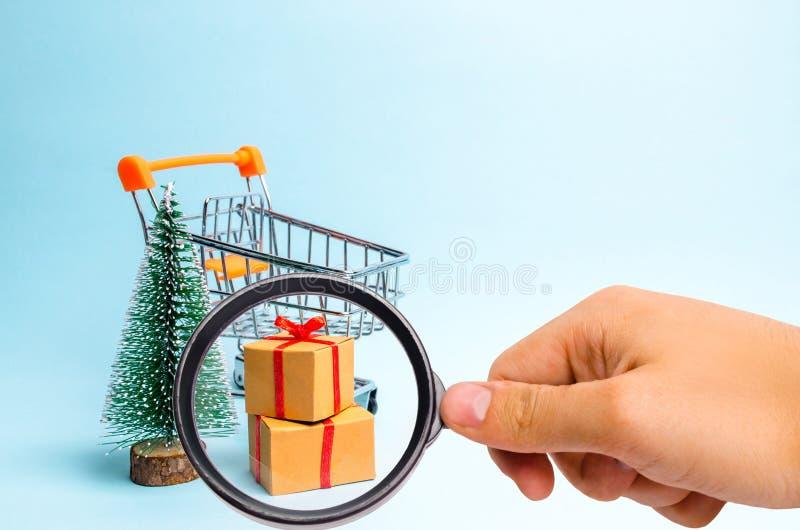 Förstoringsglaset ser julgranen, supermarketvagnen och gåvan på en blå bakgrund minimalism Isolerat på vit bakgrund fotografering för bildbyråer