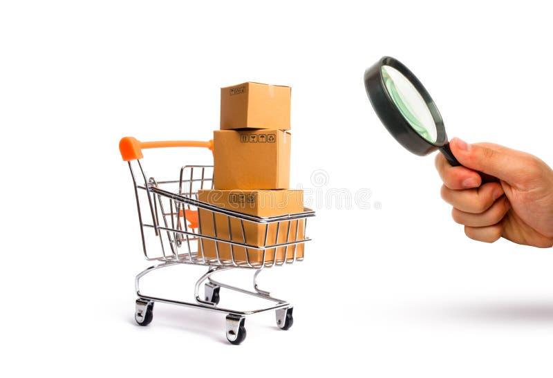 Förstoringsglaset ser supermarketvagnen med askar, varor: begreppet av att köpa och att sälja varor och tjänst royaltyfria foton