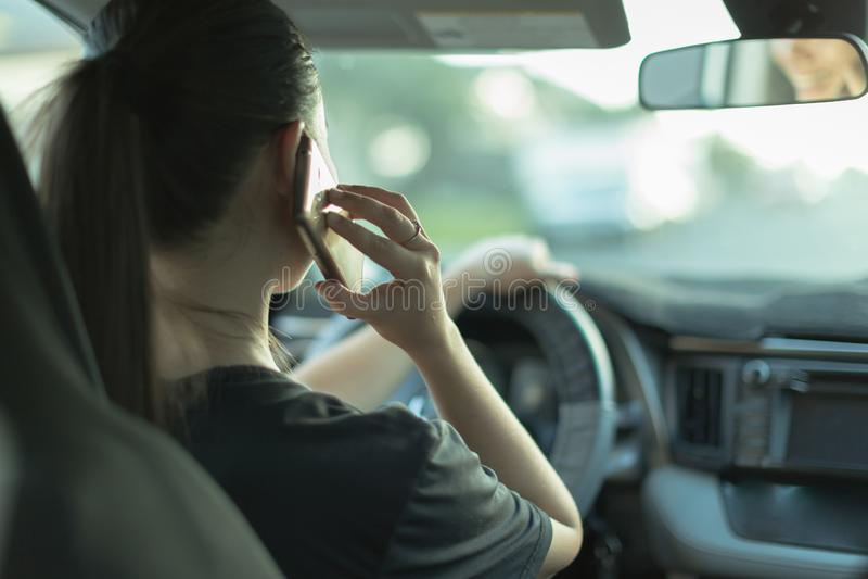 Förströdd kvinna som talar på hennes telefon, medan köra fotografering för bildbyråer