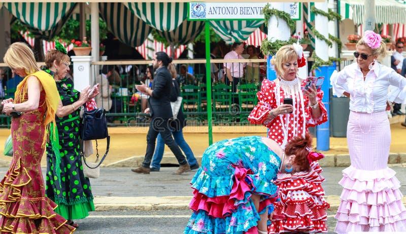 Förströdda kvinnor som bär traditionell flamenco, klär på April Fair Seville royaltyfria foton