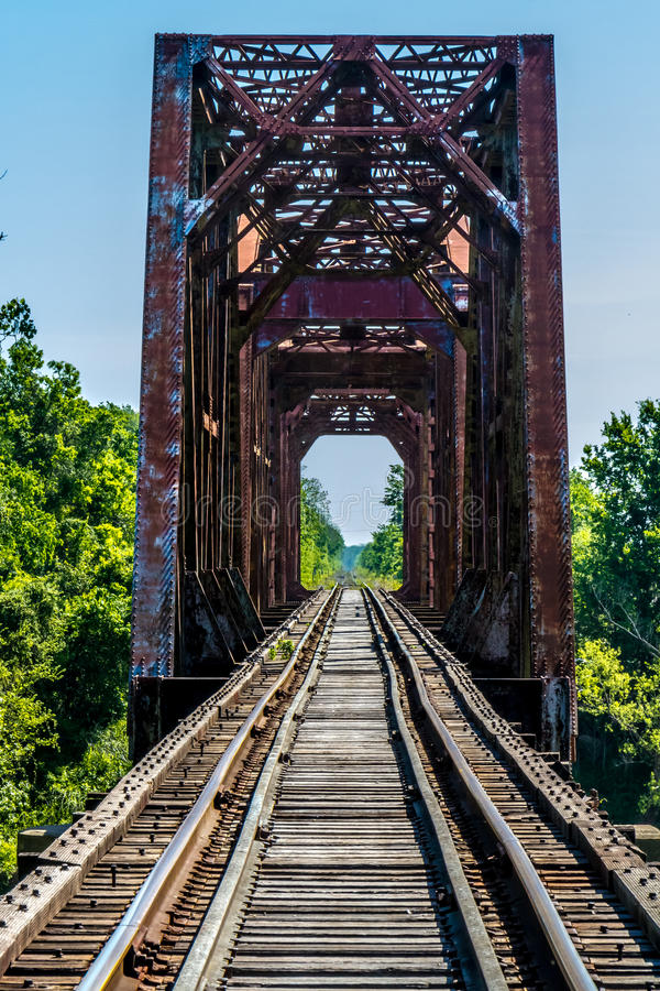 Försvinna punktsikt av en gammal järnvägbock med en gammal järnbråckbandbro över Brazoset River fotografering för bildbyråer