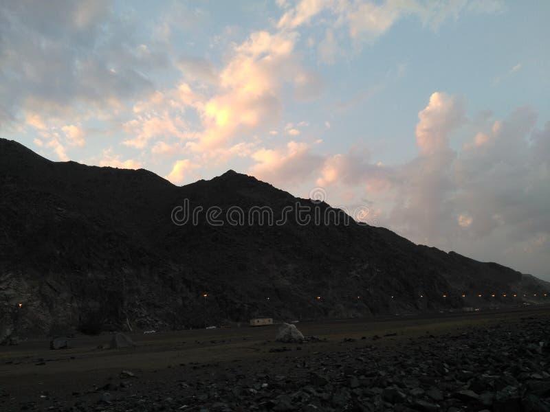 Försvinnandet av solen bak berget royaltyfri fotografi
