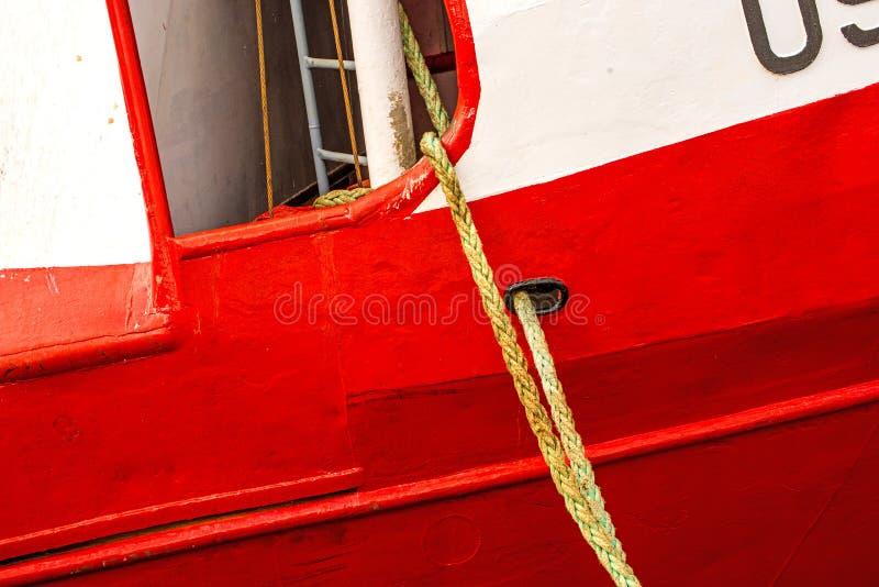 Förtöja linje av en trålare på en röd skeppskrov arkivfoton