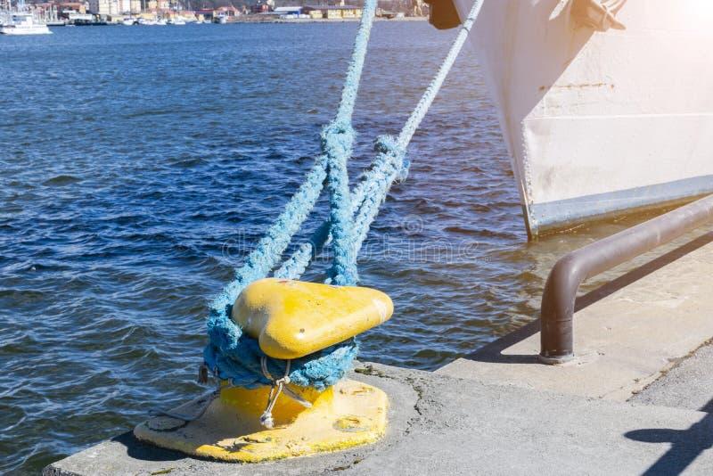 Förtöja repet som binds till pollaren på pir förtöja nautiskt rep Sändande objektbegrepp Seglingrep Gul marinapollare arkivfoton