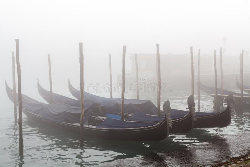 Förtöjd dimmig vintersolnedgång för blåa gondoler royaltyfria bilder