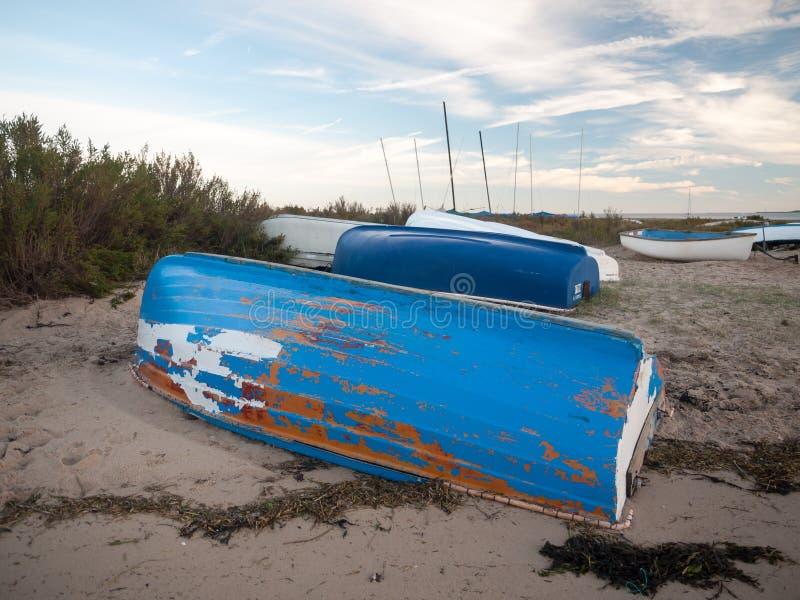 Förtöjde det uppochnervända blått gå i flisor målade privata fartyget på stranden royaltyfri bild