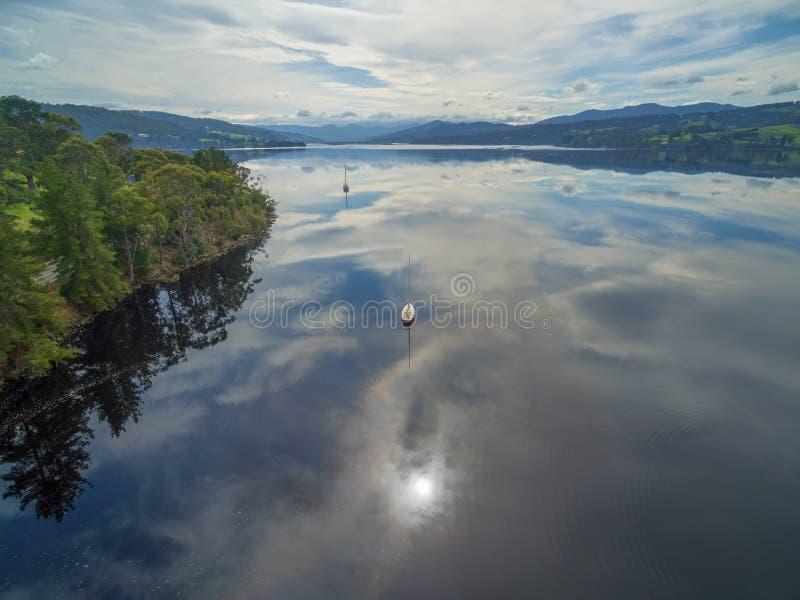 Förtöjde segelbåtar på Huon River, Huon Valley, Tasmanien, Australien royaltyfria foton