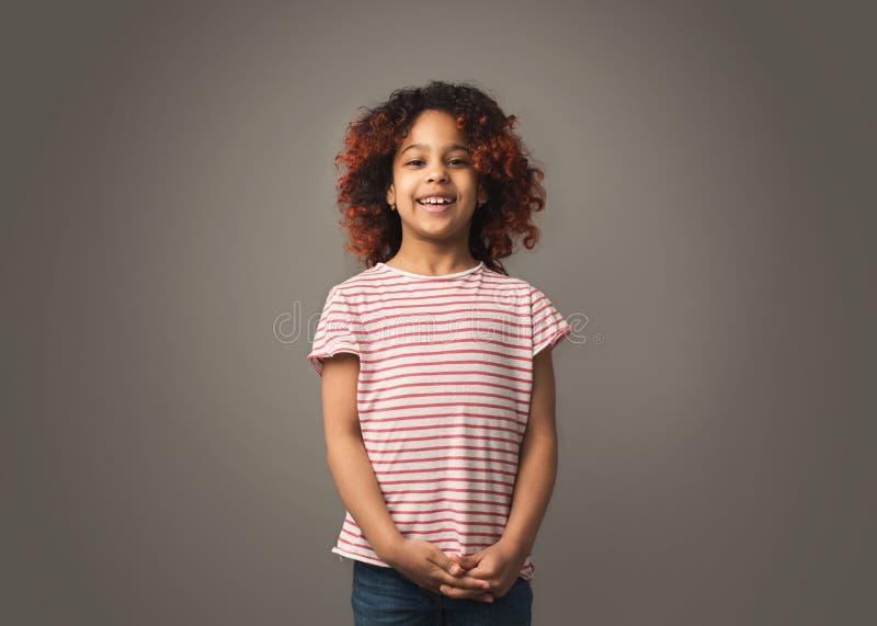 Förtjusande afrikansk liten flicka med lockigt hår över grå bakgrund arkivbilder