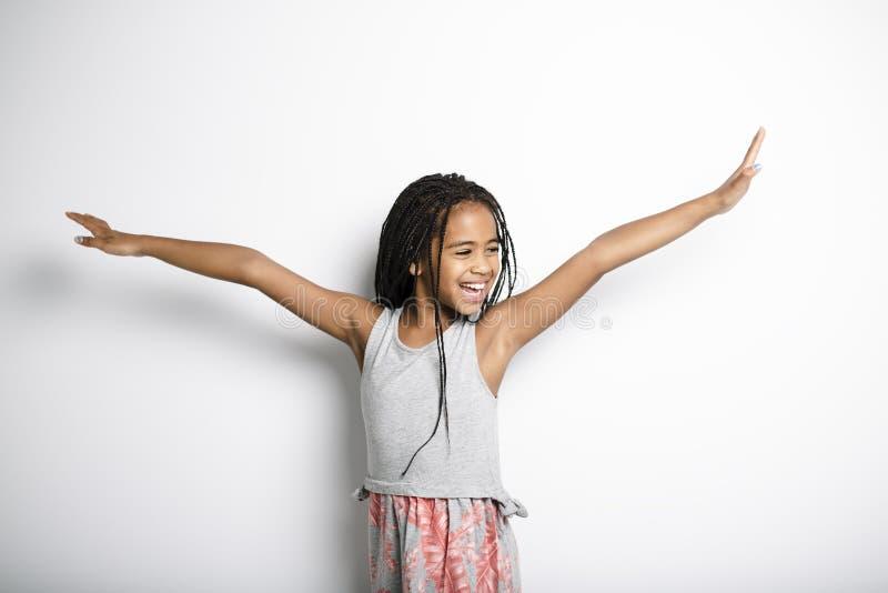 Förtjusande afrikansk liten flicka på studiogrå färgbakgrund arkivbilder