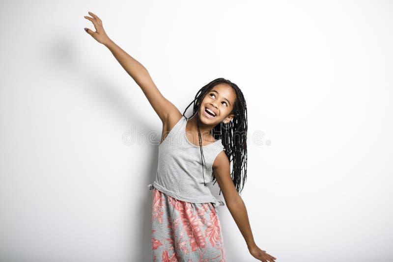 Förtjusande afrikansk liten flicka på studiogrå färgbakgrund arkivfoton