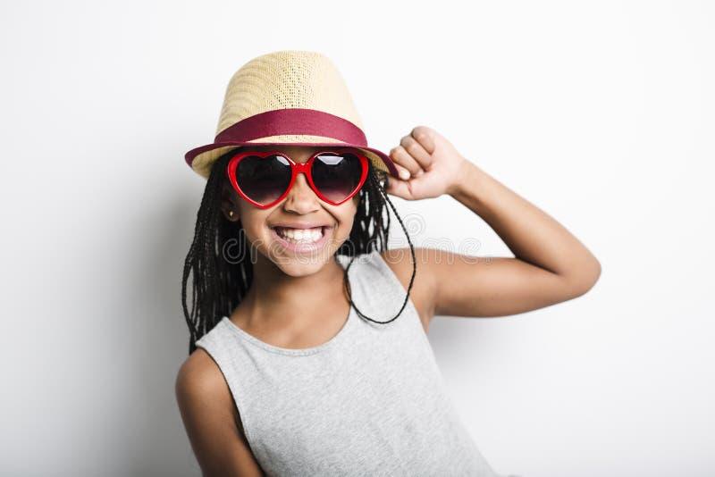 Förtjusande afrikansk liten flicka på studiogrå färgbakgrund arkivfoto