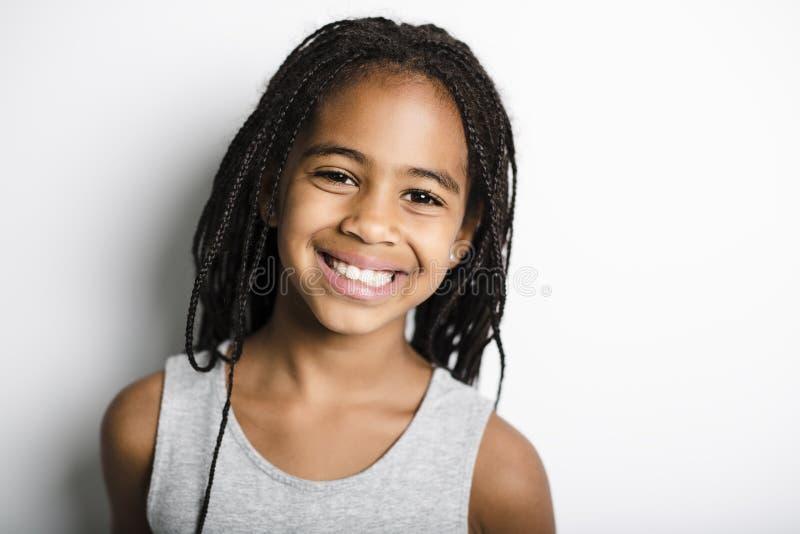 Förtjusande afrikansk liten flicka på studiogrå färgbakgrund fotografering för bildbyråer