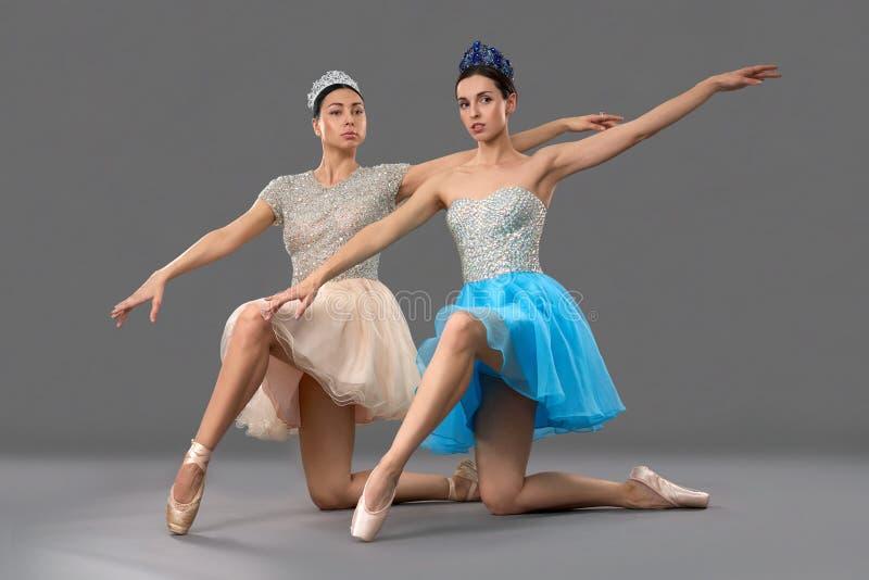 Förtjusande balettdansörer som sitter på knä och lyfter upp handen royaltyfri bild
