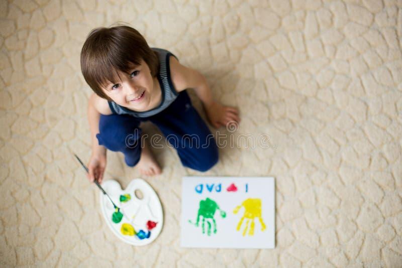 Förtjusande barn, pojke som förbereder gåvan för faderdag för farsa fotografering för bildbyråer