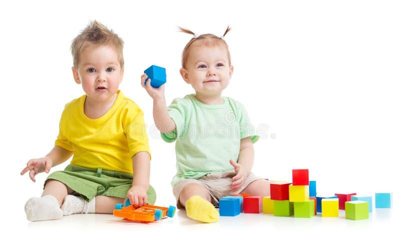 Förtjusande barn som spelar isolerade färgrika leksaker royaltyfri fotografi