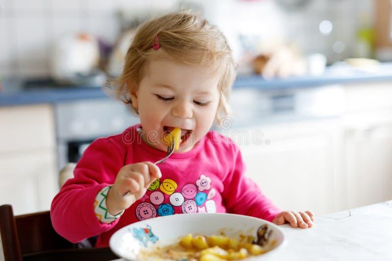 Förtjusande behandla som ett barn flickan som äter från gaffelgrönsaker och pasta mat-, barn-, matnings- och utvecklingsbegrepp royaltyfri bild