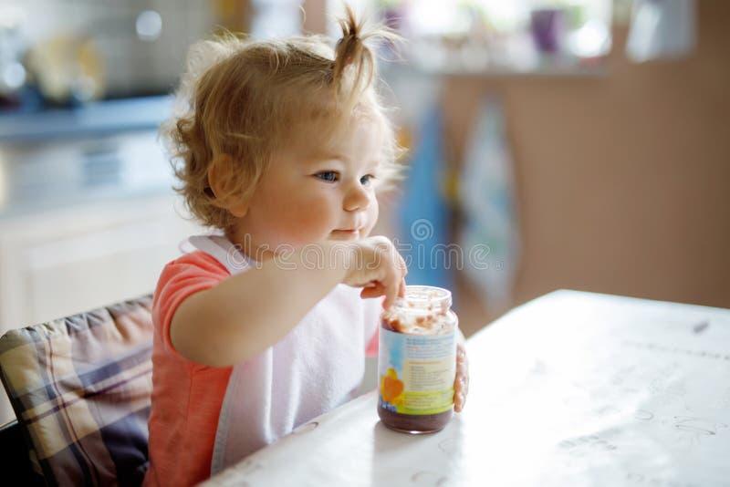 Förtjusande behandla som ett barn flickan som äter från skedgrönsaker eller, bära frukt begreppet för på burk mat, barn-, matning royaltyfria bilder