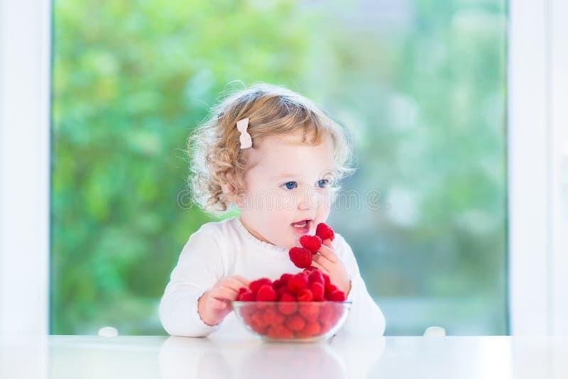 Förtjusande behandla som ett barn flickan som äter hallonet på den vita tabellen arkivbild