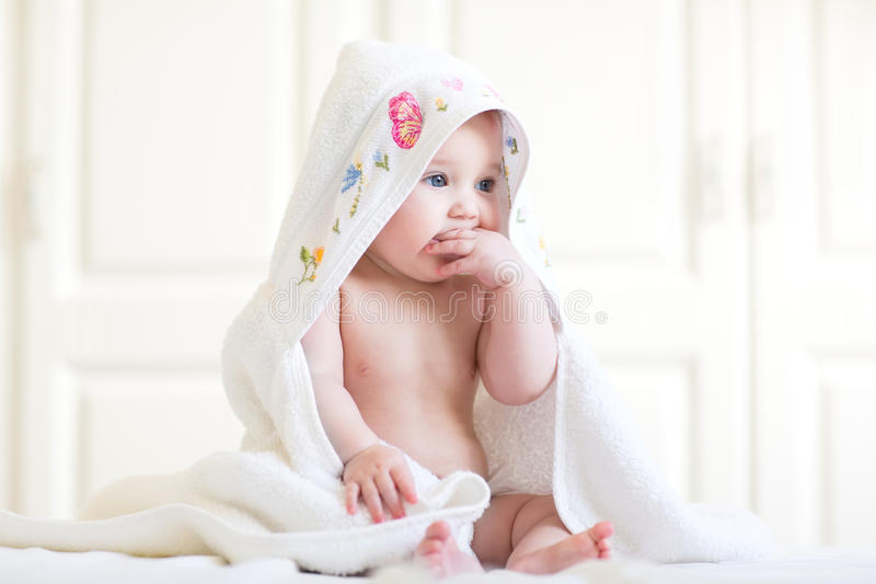 Förtjusande behandla som ett barn flickasammanträde under en med huva handduk efter bad arkivbild