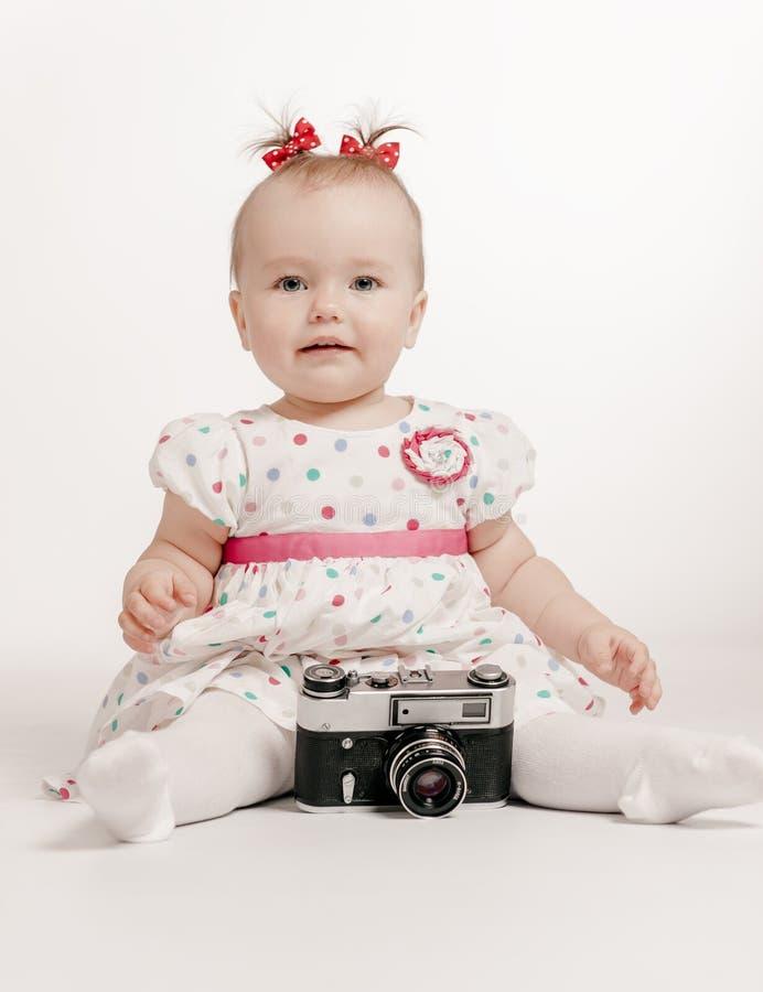 Förtjusande behandla som ett barn med den retro kameran arkivfoto
