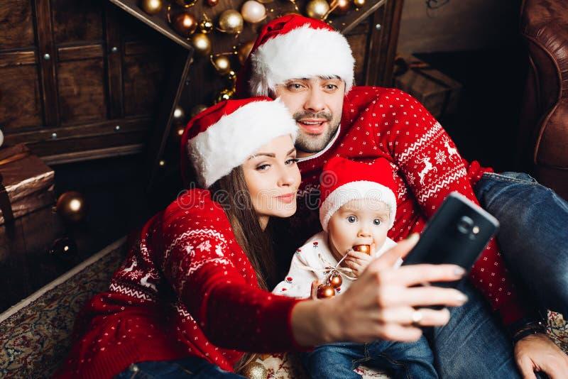 Förtjusande behandla som ett barn med föräldrar som tar selfie via mobiltelefonen royaltyfri bild
