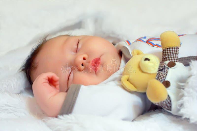 Förtjusande behandla som ett barn nyfött sova med leksaken fotografering för bildbyråer