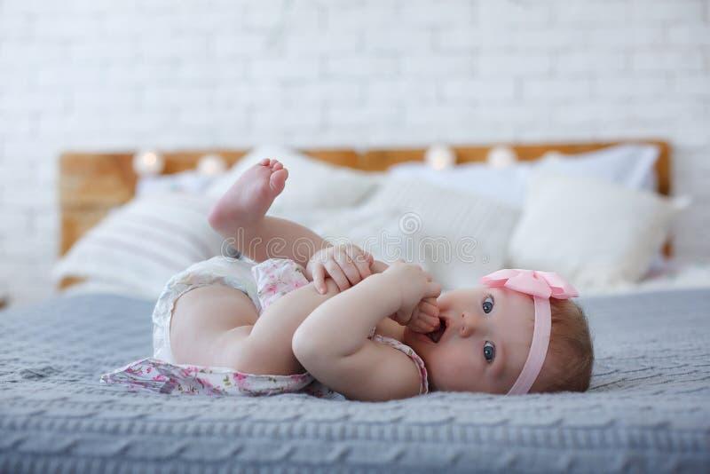 Förtjusande behandla som ett barn pojken i det vita soliga sovrummet spelar bara på sängen arkivfoto