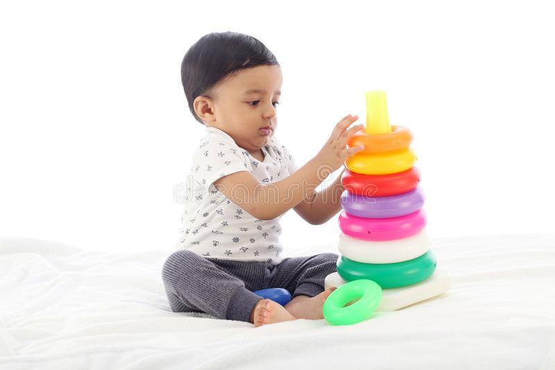Förtjusande behandla som ett barn pojken som spelar med att stapla cirklar royaltyfri fotografi