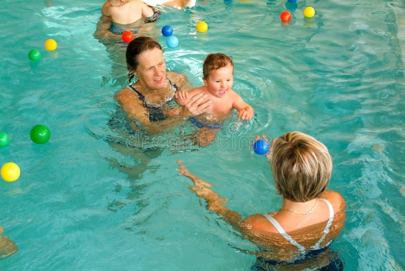 Förtjusande behandla som ett barn tycka om att simma i en pöl med hans moder arkivbilder