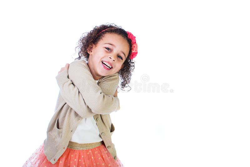 Förtjusande biracial flicka som kramar hon själv royaltyfria bilder