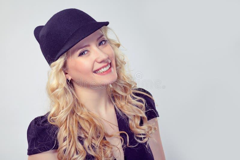 Förtjusande blond kvinna i stilfull hatt arkivbild