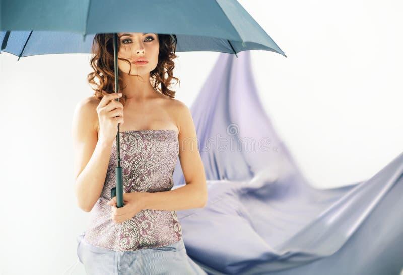 Förtjusande brunettkvinna som rymmer ett paraply royaltyfri bild