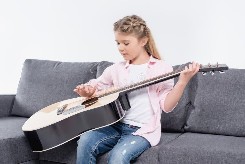 Förtjusande caucasian flicka som spelar på gitarren, medan sitta på soffan arkivfoton