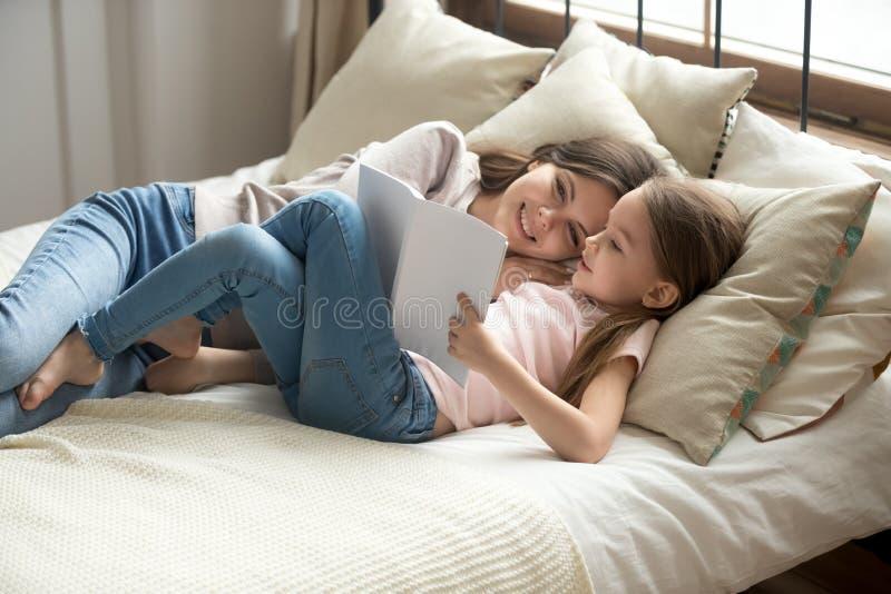 Förtjusande dotter och moder som vilar att ligga på sängläseboken royaltyfri bild