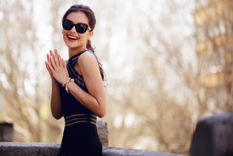 Förtjusande elegant brunett i sexig svart klänning, solglasögon, hårhästsvans och härligt framsidastag på balkongen arkivbild