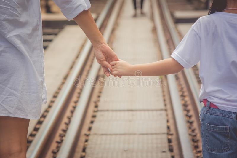Förtjusande familjbegrepp: Kvinna och barn som går på järnvägspår och innehavhanden samman med att se som ska eftersändas royaltyfria foton