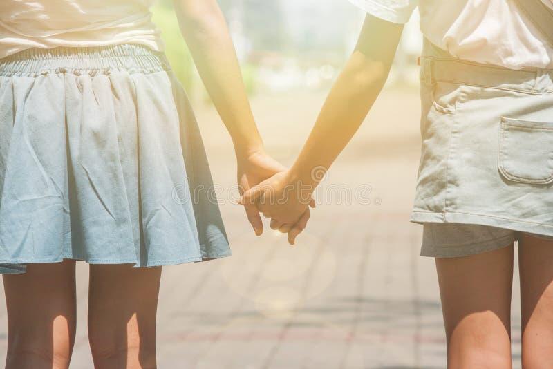 Förtjusande familjbegrepp: Två systrar som går på gångbanan på offentligt, parkerar och tillsammans rymmer handen royaltyfria bilder