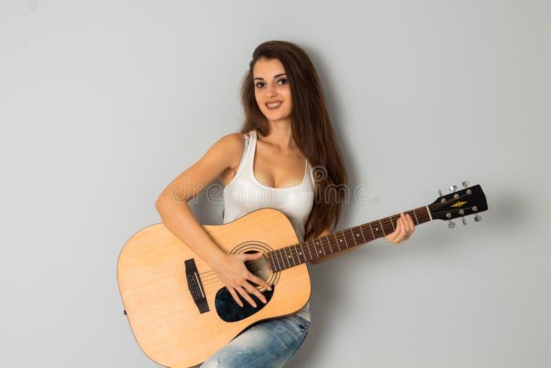 Förtjusande flicka med gitarren i händer royaltyfri bild