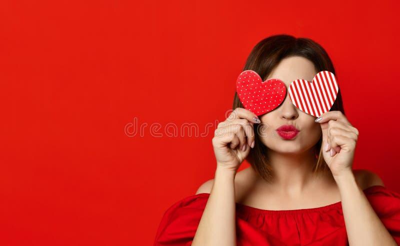 Förtjusande flicka med valentin daghjärta som visar ståenden för förälskelsegyckelaffektion royaltyfria bilder