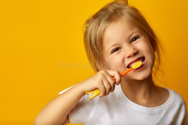 Förtjusande flicka som borstar tänder med ungetandborsten royaltyfri fotografi